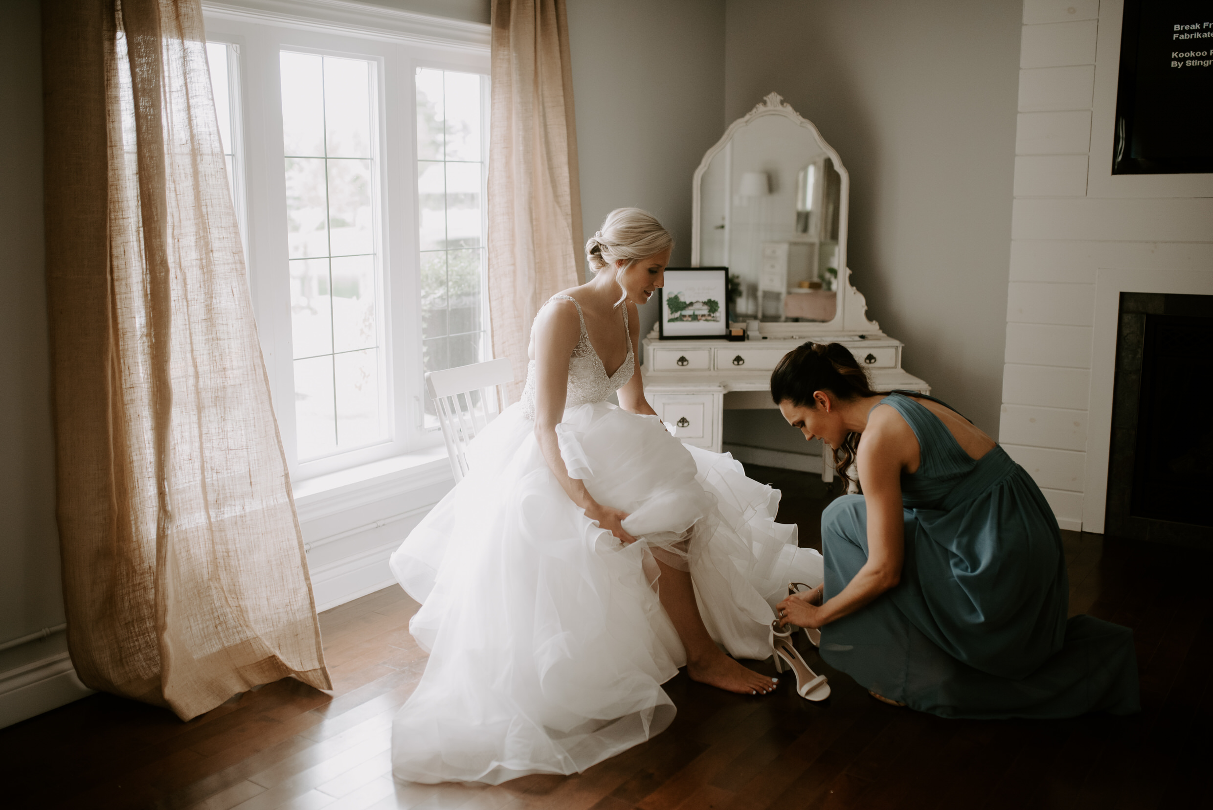 Belcroft Estates Wedding - bridesmaid helping bride with shoes