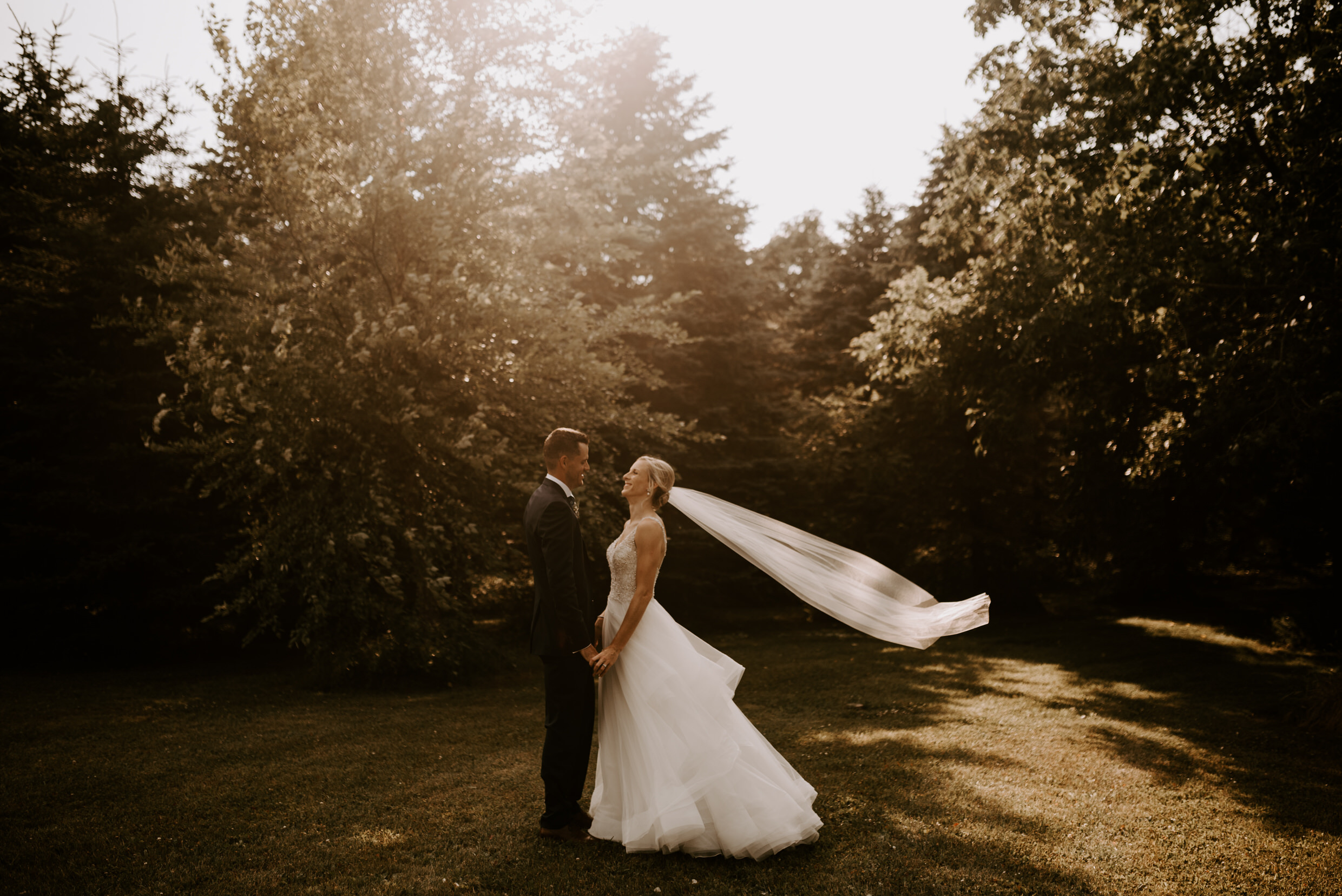 Belcroft Estates Wedding - Bride and groom in forest with blowing veil